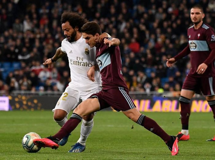 Real Madrids Brazilian defender Marcelo (L) challenges Celta Vigos Spanish midfielder Denis Suarez during the Spanish league football match between Real Madrid CF and RC Celta de Vigo at the Santiago Bernabeu stadium in Madrid on February 16, 2020. (Photo by PIERRE-PHILIPPE MARCOU / AFP)