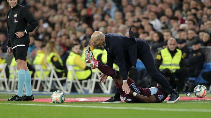 Real Madrids head coach Zinedine Zidane falls with Celta Vigos Joseph Aidoo during the Spanish La Liga soccer match between Real Madrid and Celta de Vigo at the Santiago Bernabeu stadium in Madrid, Spain, Sunday, Feb. 16, 2020. (AP Photo/Manu Fernandez)