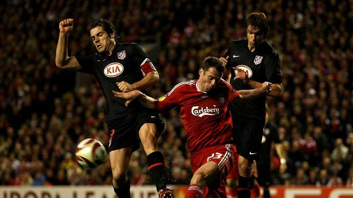 LIVERPOOL, ENGLAND - APRIL 29:   Jamie Carragher of Liverpool clears under pressure from Antonio Lopez of Atletico Madrid during the UEFA Europa League Semi-Final Second Leg match between Liverpool and Atletico Madrid at Anfield on April 29, 2010 in Liverpool, England.  (Photo by Clive Brunskill/Getty Images)