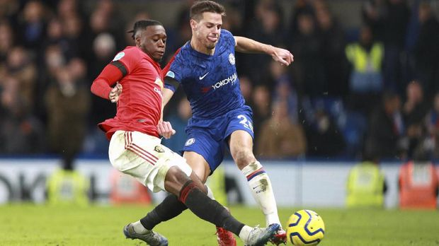 Manchester United's Aaron Wan-Bissaka, left, attempts a tackle on Chelsea's Cesar Azpilicueta during the English Premier League soccer match between Chelsea and Manchester United at Stamford Bridge in London, England, Monday, Feb. 17, 2020. (AP Photo/Ian Walton)