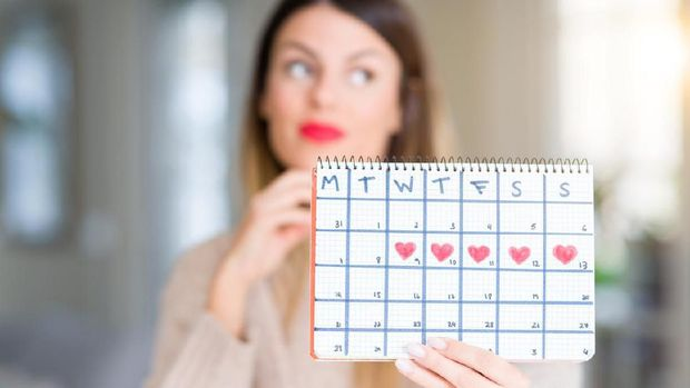 Young beautiful woman holding menstruation calendar at home serious face thinking about question, very confused idea