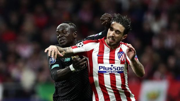 Liverpool's Sadio Mane, left, stops Atletico Madrid's Sime Vrsaljko during a 1st leg, round of 16, of the Champions League soccer match between Atletico Madrid and Liverpool at the Wanda Metropolitano stadium in Madrid, Tuesday, Feb. 18, 2020. (AP Photo/Manu Fernandez)