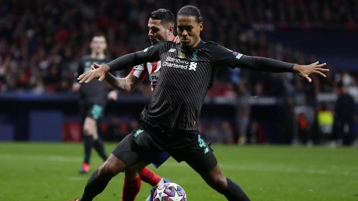 Liverpools Virgil van Dijk, foreground, controls the ball past Atletico Madrids Sime Vrsaljko during a 1st leg, round of 16, of the Champions League soccer match between Atletico Madrid and Liverpool at the Wanda Metropolitano stadium in Madrid, Tuesday, Feb. 18, 2020. (AP Photo/Manu Fernandez)