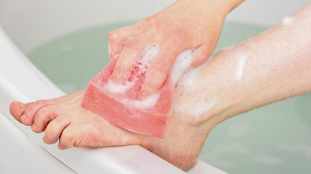 Caucasian woman washing her leg and foot in a bathtub using a pink bathing sponge.