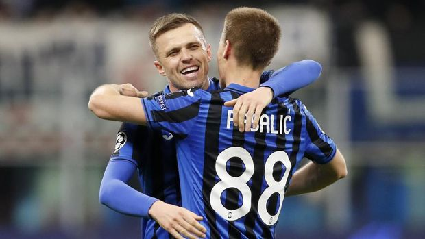 Atalanta's Josip Ilicic, left, scores his side's second goal during the Champions League round of 16, first leg, soccer match between Atalanta and Valencia at the San Siro stadium in Milan, Italy, Wednesday, Feb. 19, 2020. (AP Photo/Antonio Calanni)