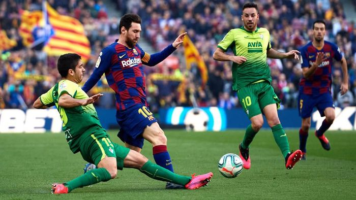 BARCELONA, SPAIN - FEBRUARY 22: Jose Angel Valdes Cote of SD Eibar tackles Lionel Messi of FC Barcelona during the La Liga match between FC Barcelona and SD Eibar SAD at Camp Nou on February 22, 2020 in Barcelona, Spain. (Photo by Alex Caparros/Getty Images)
