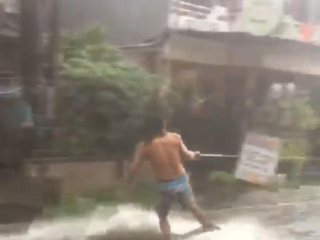 Ditarik Motor, Pria Ini Asyik Surfing di Tengah Banjir