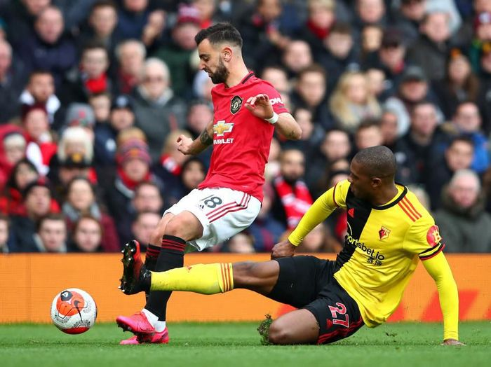 MANCHESTER, ENGLAND - FEBRUARY 23: Christian Kabasele of Watford tackles Bruno Fernandes of Manchester United during the Premier League match between Manchester United and Watford FC at Old Trafford on February 23, 2020 in Manchester, United Kingdom. (Photo by Clive Brunskill/Getty Images)