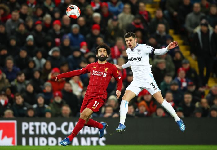 LIVERPOOL, ENGLAND - FEBRUARY 24: Mohamed Salah of Liverpool challenges for the high ball with Aaron Cresswell of West Ham United during the Premier League match between Liverpool FC and West Ham United at Anfield on February 24, 2020 in Liverpool, United Kingdom. (Photo by Clive Brunskill/Getty Images)