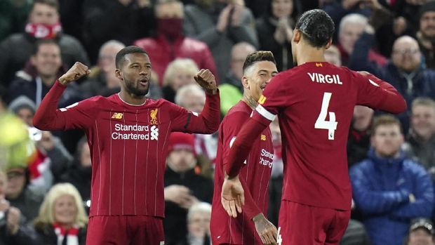 Liverpool's Georginio Wijnaldum, left, celebrates with teammate Virgil van Dijk after scoring his team's first goal during the English Premier League soccer match between Liverpool and West Ham at Anfield Stadium in Liverpool, England, Monday, Feb. 24, 2020. (AP Photo/Jon Super)