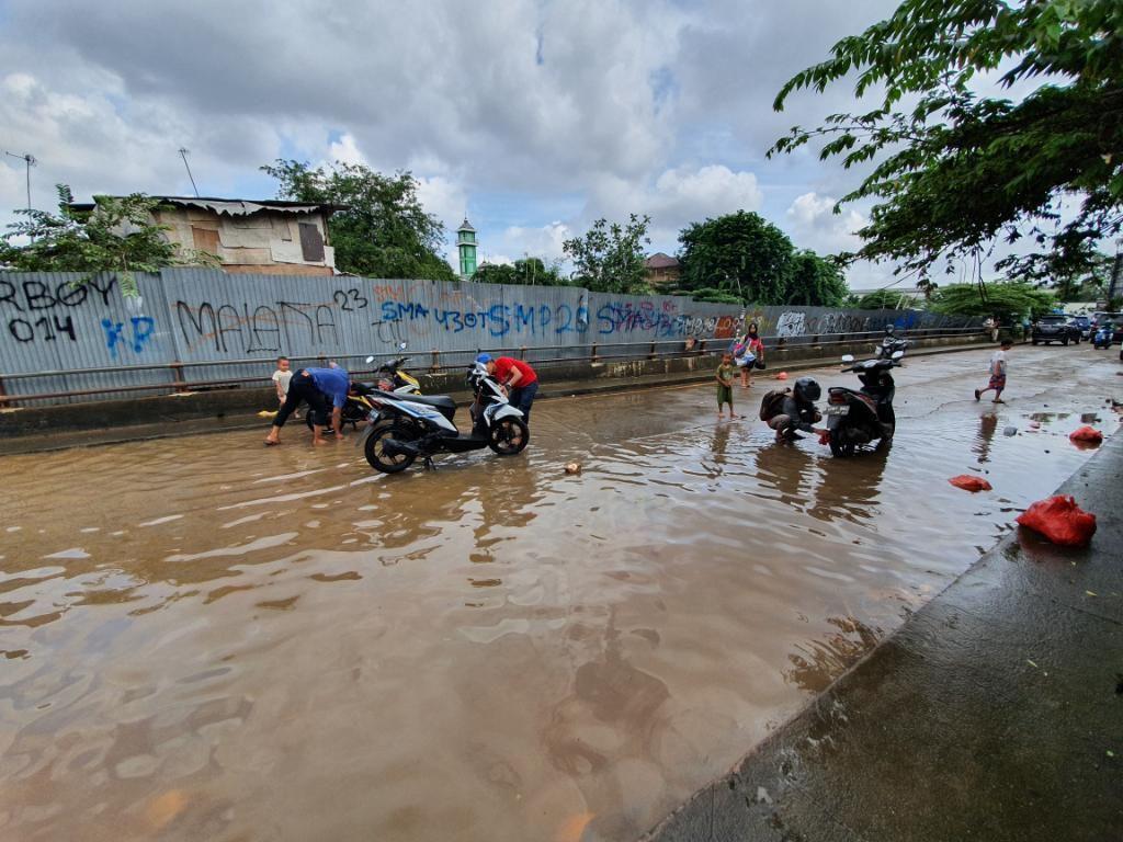 Saat Warga Bekasi Memanfaatkan Air Banjir untuk Cuci Motor