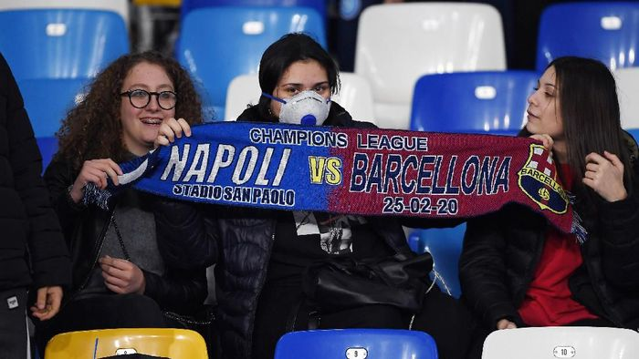 NAPLES, ITALY - FEBRUARY 25: SSC Napoli supporters, one of them with a mask due to Coronavirus, show a scarf before the UEFA Champions League round of 16 first leg match between SSC Napoli and FC Barcelona at Stadio San Paolo on February 25, 2020 in Naples, Italy. (Photo by Francesco Pecoraro/Getty Images)