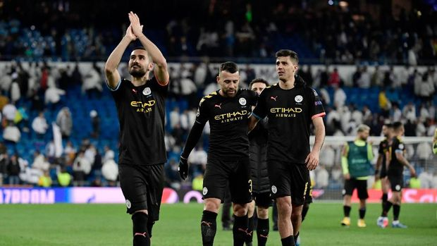 Mnachester City's players celebrate their win at the end of the UEFA Champions League round of 16 first-leg football match between Real Madrid CF and Manchester City at the Santiago Bernabeu stadium in Madrid on February 26, 2020. (Photo by JAVIER SORIANO / AFP)