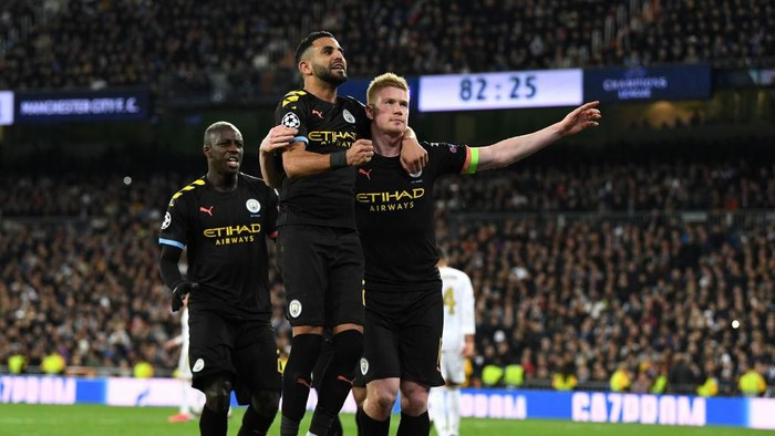 MADRID, SPAIN - FEBRUARY 26: Kevin De Bruyne of Manchester City celebrates with teammate Riyad Mahrez after scoring his teams second goal during the UEFA Champions League round of 16 first leg match between Real Madrid and Manchester City at Bernabeu on February 26, 2020 in Madrid, Spain. (Photo by David Ramos/Getty Images)