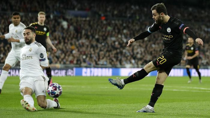 Real Madrids Dani Carvajal, left, tries to block a shot from Manchester Citys Bernardo Silva during the Champions League, round of 16, first leg soccer match between Real Madrid and Manchester City at the Santiago Bernabeu stadium in Madrid, Spain, Wednesday, Feb. 26, 2020. (AP Photo/Manu Fernandez)