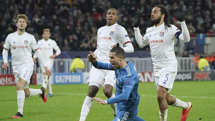 Juventus Cristiano Ronaldo goes down in the penalty box after contact with Lyons Jason Denayer, right, during a round of sixteen, first leg, soccer match between Lyon and Juventus at the at the Lyon Olympic Stadium in Decines, outside Lyon, France, Wednesday, Feb. 26, 2020. (AP Photo/Laurent Cipriani)