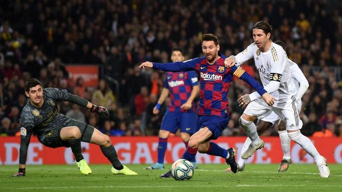 BARCELONA, SPAIN - DECEMBER 18:  Lionel Messi of Barcelona holds off Sergio Ramos of Real Madrid during the Liga match between FC Barcelona and Real Madrid CF at Camp Nou on December 18, 2019 in Barcelona, Spain. (Photo by Alex Caparros/Getty Images)