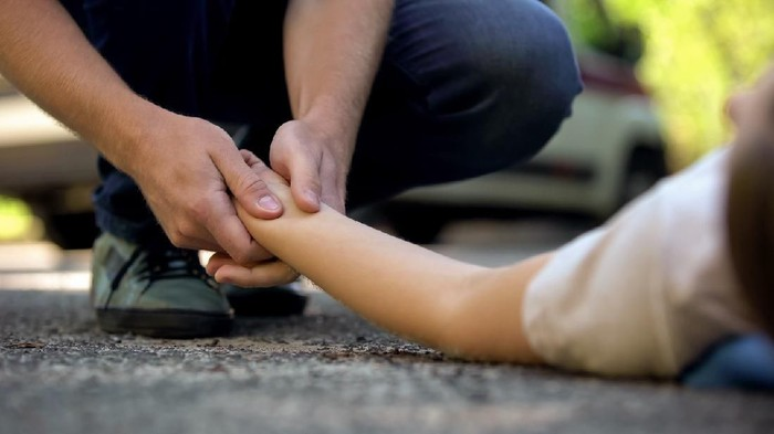 Man holding hand of girl lying on road, unconscious victim of car accident, 911
