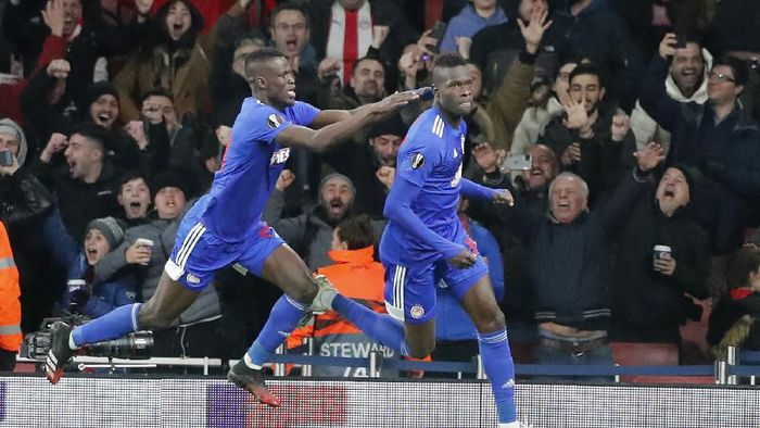 Olympiakos Pape Abou Cisse, right, celebrates after scoring during the Europa League round of 32, second leg, soccer match between Arsenal and Olympiakos at Emirates stadium in London, England, Thursday, Feb. 27, 2020 . (AP Photo/Frank Augstein)