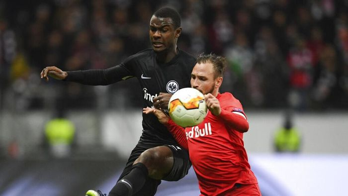 Frankfurts Evan NDicka, left, and Salzburgs Andreas Ulmer battle for the ball during the Europa League round of 32 first leg soccer match between Eintracht Frankfurt and FC Red Bull Salzburg at the Commerzbank-Arena in Frankfurt, Germany, Thursday, Feb. 20, 2020. (Arne Dedert/dpa via AP)