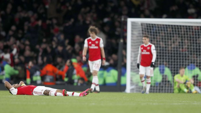 Arsenal players react after losing the Europa League round of 32, second leg, soccer match between Arsenal and Olympiakos at Emirates stadium in London, England, Thursday, Feb. 27, 2020 . (AP Photo/Frank Augstein)