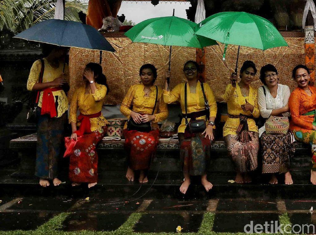 Semangat Umat Hindu Beribadah di Tengah Hujan Deras