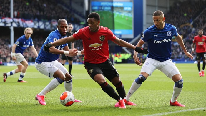 LIVERPOOL, ENGLAND - MARCH 01: Anthony Martial of Manchester United is challenged by Djibril Sidibe and Richarlison of Everton during the Premier League match between Everton FC and Manchester United at Goodison Park on March 01, 2020 in Liverpool, United Kingdom. (Photo by Clive Brunskill/Getty Images)