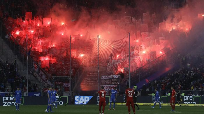 Bayerns fans light flares during a German Bundesliga soccer match between TSG 1899 Hoffenheim and Bayern Munich in Sinsheim, Germany, Saturday, Feb. 29, 2020. (AP Photo/Michael Probst)