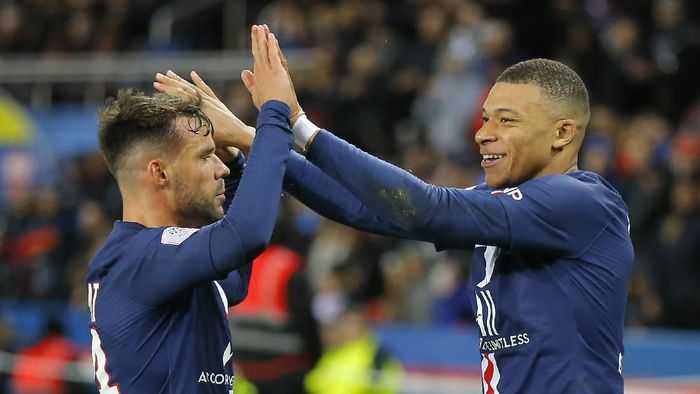 PSGs Kylian Mbappe, right, celebrates with teammate Juan Bernat after scoring his sides fourth goal during the French League One soccer match between Paris-Saint-Germain and Dijon, at the Parc des Princes stadium in Paris, France, Saturday, Feb. 29, 2020. (AP Photo/Michel Euler)