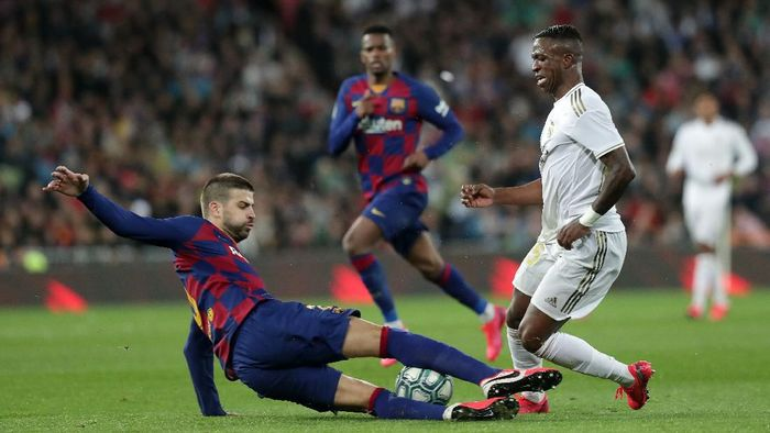 MADRID, SPAIN - MARCH 01: Gerard Pique of FC Barcelona tackles Vinicius Junior of Real Madrid during the Liga match between Real Madrid CF and FC Barcelona at Estadio Santiago Bernabeu on March 01, 2020 in Madrid, Spain. (Photo by Gonzalo Arroyo Moreno/Getty Images)