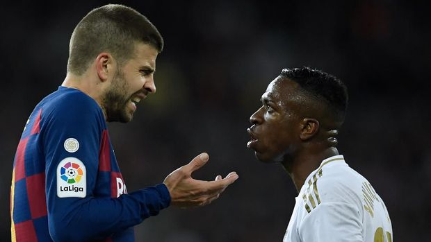 Barcelona's Spanish defender Gerard Pique (L) talks with Real Madrid's Brazilian forward Vinicius Junior during the Spanish League football match between Real Madrid and Barcelona at the Santiago Bernabeu stadium in Madrid on March 1, 2020. (Photo by OSCAR DEL POZO / AFP)