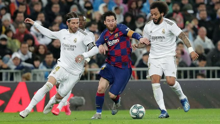 MADRID, SPAIN - MARCH 01: Lionel Messi of FC Barcelona controls the ball while challenged by Sergio Ramos of Real Madrid and Marcelo of Real Madrid during the Liga match between Real Madrid CF and FC Barcelona at Estadio Santiago Bernabeu on March 01, 2020 in Madrid, Spain. (Photo by Gonzalo Arroyo Moreno/Getty Images)