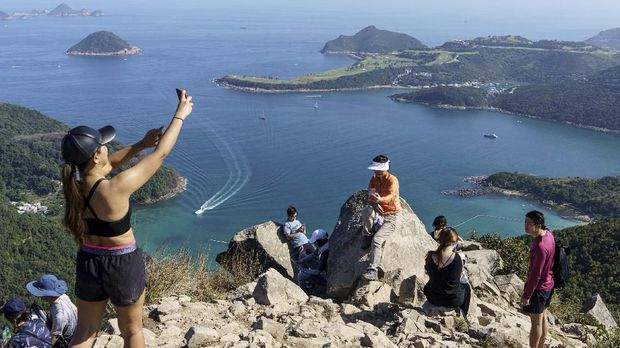 In this picture taken on February 29, 2020, hikers take pictures on High Junk Peak overlooking Clearwater Bay in the Tsuen Kwan O area of Hong Kong. - Remote hiking trails are offering Hong Kongers an open-air escape from the coronavirus fears that have engulfed the densely-populated city and triggered the closure of public facilities and schools. (Photo by Yan ZHAO / AFP) / To go with AFP story Hong Kong-health-virus-lifestyle by Yan Zhao