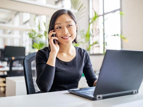 Young asian businesswoman sitting at her desk with laptop talking on mobile phone. Female professional working in modern office.