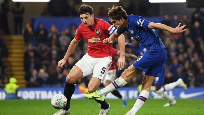 LONDON, ENGLAND - OCTOBER 30: Marcos Alonso of Chelsea shoots under pressure from Harry Maguire of Manchester United during the Carabao Cup Round of 16 match between Chelsea and Manchester United at Stamford Bridge on October 30, 2019 in London, England. (Photo by Mike Hewitt/Getty Images)