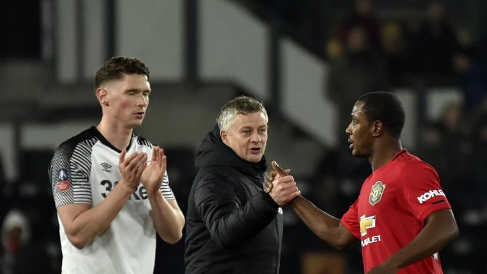 Manchester Uniteds manager Ole Gunnar Solskjaer, center, shakes hands with Manchester Uniteds Odion Ighalo, right, at the end of the FA Cup fifth round soccer match between Derby County and Manchester United at Pride Park in Derby, England, Thursday, March 5, 2020. (AP Photo/Rui Vieira)