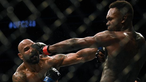 LAS VEGAS, NEVADA - MARCH 07: Israel Adesanya and Yoel Romero exchange punches in a Adesanya decision win to retain the middleweight title at T-Mobile Arena on March 07, 2020 in Las Vegas, Nevada.   Harry How/Getty Images/AFP