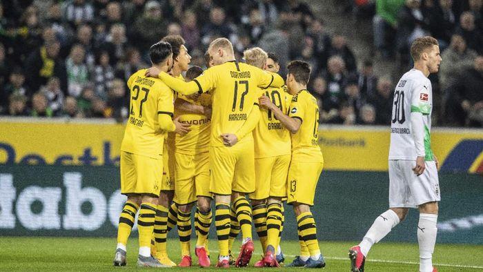 Dortmund players celebrate scoring during the Bundesliga soccer match between Borussia Monchengladbach and Borussia Dortmund, at Borussia Park, Monchengladbach, Germany, Saturday March 7, 2020. (Bernd Thissen/dpa via AP)