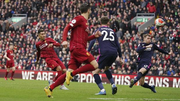 Liverpool's Roberto Firmino, left, attempts a shot on goal during the English Premier League soccer match between Liverpool and Bournemouth at Anfield stadium in Liverpool, England, Saturday, March 7, 2020. (AP Photo/Jon Super)
