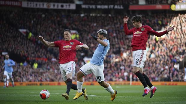 Manchester City's Sergio Aguero, center, and Manchester United's Nemanja Matic, left, and Victor Lindelof compete for the ball during the English Premier League soccer match between Manchester United and Manchester City at Old Trafford in Manchester, England, Sunday, March 8, 2020. (AP Photo/Dave Thompson)