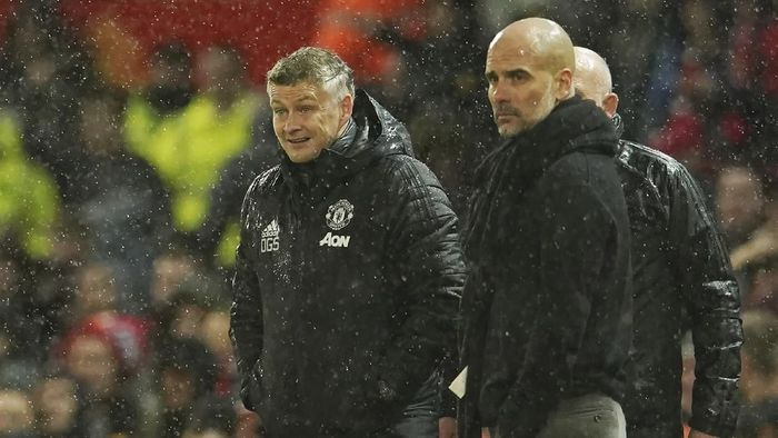 Manchester Uniteds manager Ole Gunnar Solskjaer, left, and Manchester Citys head coach Pep Guardiola watch the English Premier League soccer match between Manchester United and Manchester City at Old Trafford in Manchester, England, Sunday, March 8, 2020. (AP Photo/Dave Thompson)