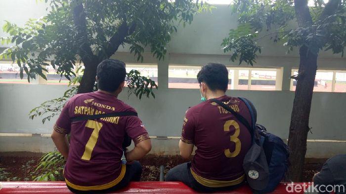 Suporter PSM mendukung tim kesayangan dari celah tembok stadion Madya