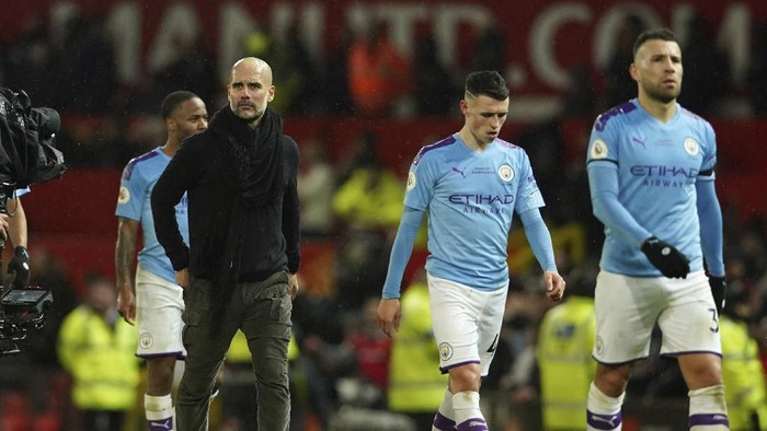 Manchester Citys head coach Pep Guardiola, second from left, and team players leave the pitch after the English Premier League soccer match between Manchester United and Manchester City at Old Trafford in Manchester, England, Sunday, March 8, 2020. Manchester United won 2-0. (AP Photo/Dave Thompson)