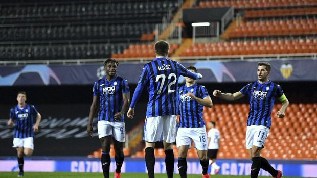 Atalanta's Josip Ilicic celebrates with teammates after scoring his side's fourth goal during the Champions League round of 16 second leg soccer match between Valencia and Atalanta in Valencia, Spain, Tuesday March 10, 2020. The match is being in an empty stadium because of the coronavirus outbreak. (UEFA via AP)