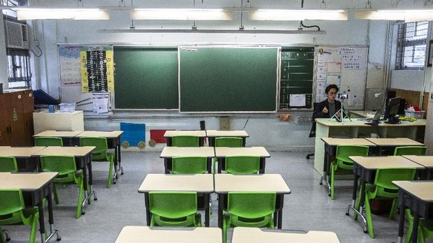 In this photo taken on March 6, 2020, primary school teacher Billy Yeung records a video lesson for his students who have had their classes suspended due to the COVID-19 coronavirus, in his empty classroom in Hong Kong. - In Hong Kong, schools have been shut since early February, with the closure now set to last until after Easter. Many teachers are turning to conference call applications to interact with students, but that requires good WiFi access and computer literacy. (Photo by ISAAC LAWRENCE / AFP) / TO GO WITH AFP STORY CHILDREN-EDUCATION-HEALTH-VIRUS-CHINA-JAPAN-SKOREA-HONG KONG-SINGAPORE,FOCUS