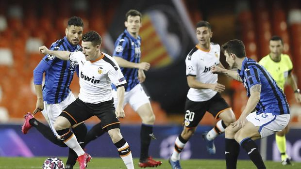 Valencia's Kevin Gameiro, left, controls the ball during the Champions League round of 16 second leg soccer match between Valencia and Atalanta in Valencia, Spain, Tuesday March 10, 2020. The match is being in an empty stadium because of the coronavirus outbreak. (UEFA via AP)