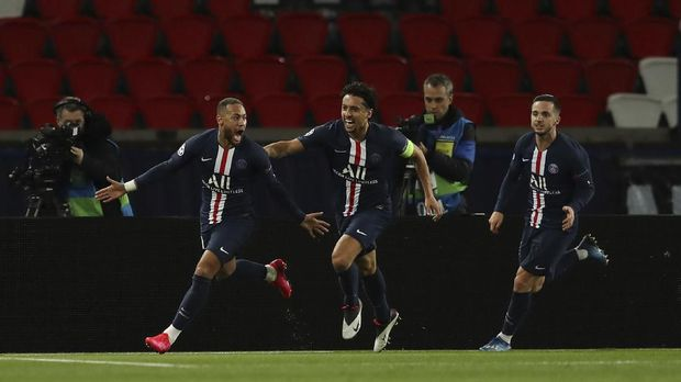 Paris Saint Germain's Neymar celebrates with teammate Marquinhos, center, after scoring his side's first goal during the Champions League round of 16 second leg soccer match between PSG and Borussia Dortmund, Wednesday March 11, 2020 in Paris. The match is being played in an empty stadium because of the coronavirus outbreak. (UEFA via AP)