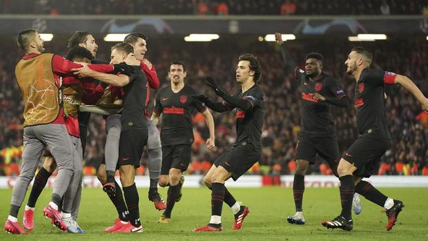 Atletico Madrid's Marcos Llorente, center, celebrates after scoring his side's opening goal during a second leg, round of 16, Champions League soccer match between Liverpool and Atletico Madrid at Anfield stadium in Liverpool, England, Wednesday, March 11, 2020. (AP Photo/Jon Super)