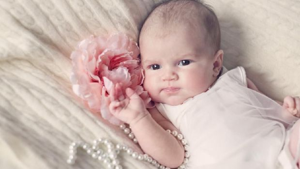 Newborn baby girl in fashionable dress with flower and pearl beads