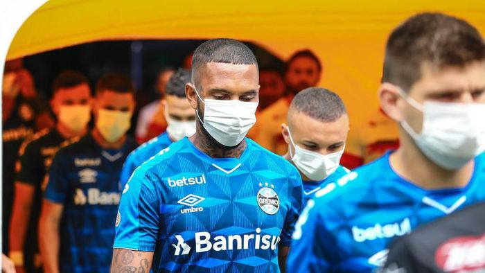 PORTO ALEGRE, BRAZIL - MARCH 15: Players of Gremio enter the field wearing masks before the match between Gremio and Sao Luiz as part of the Rio Grande do Sul State Championship 2020, to be played behind closed doors at Arena do Gremio Stadium, on March 15, 2020 in Porto Alegre, Brazil. The Government of the State of Rio Grande do Sul issued a list of new guidelines to help prevent the spread of the Coronavirus which included games played with closed doors and no public. According to the Ministry of Health, as of Saturday, March 14, Brazil had 121 confirmed cases of coronavirus. (Photo by Lucas Uebel/Getty Images)